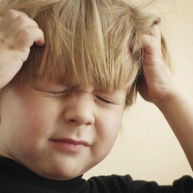 Et barn med hodelus klør seg i hodet